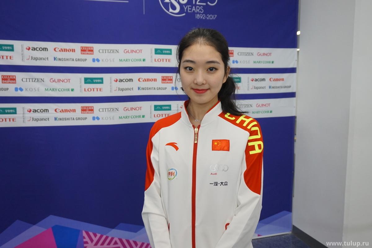 李子君 (Li Zijun) с сотрясом после произвольной программы нашла силы улыбнуться для снимка