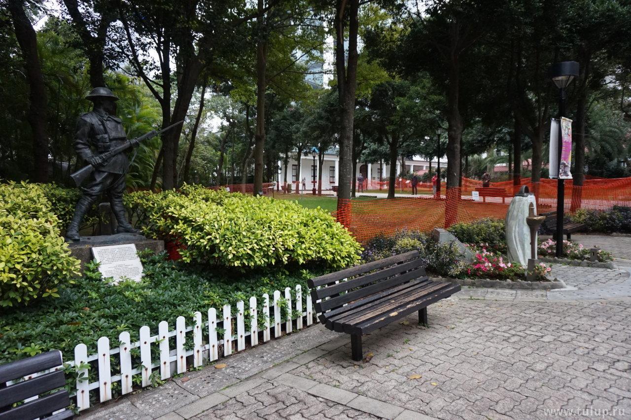 Памятник британскому солдату, питьевой фонтанчик и люди занимающиеся гимнастикой Тайцзи вдалеке