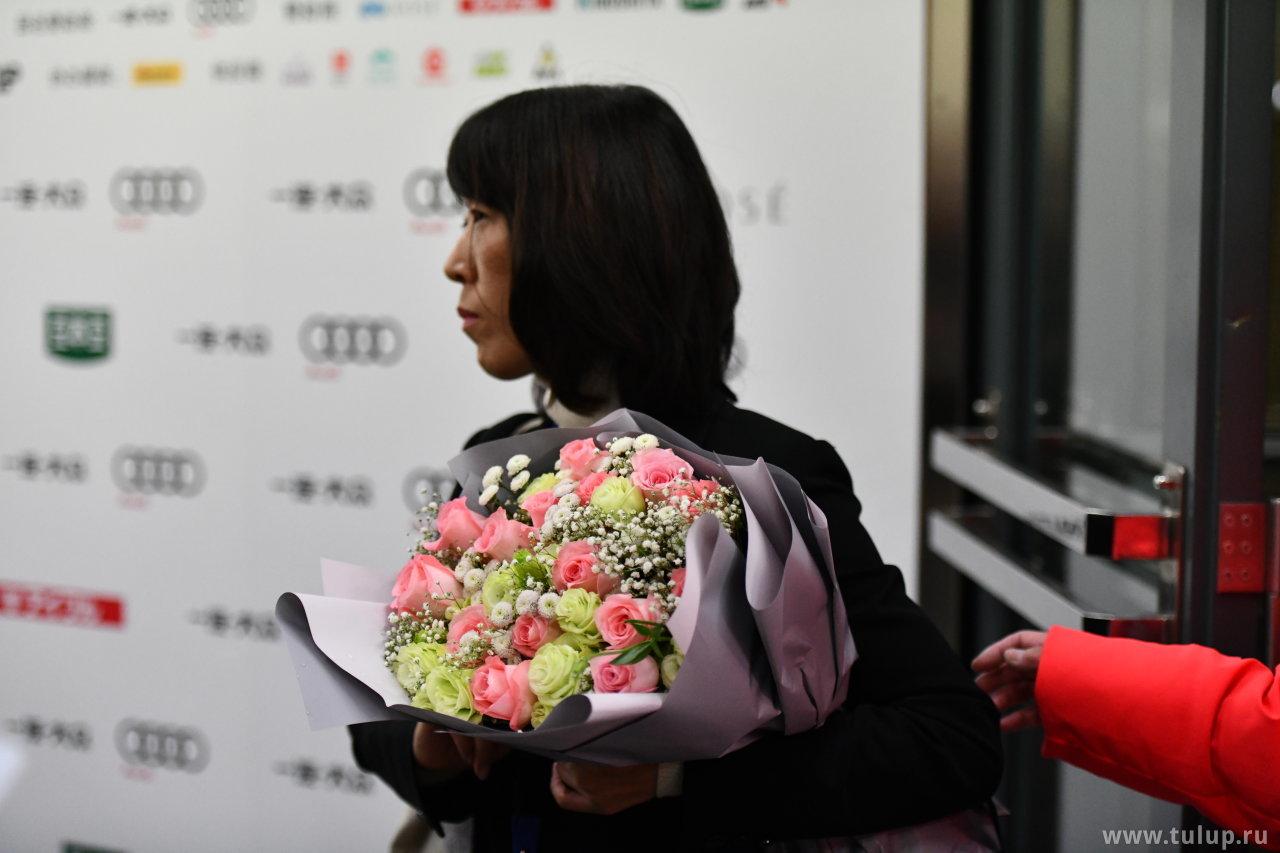 Капитан японской команды с букетом роз